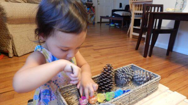 Child painting pinecones