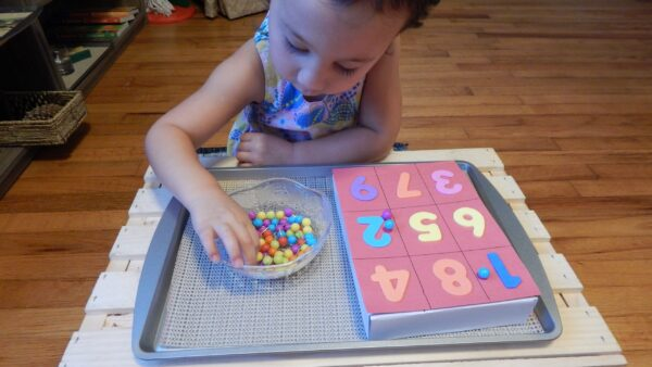 child pushing push pins into cardboard for 1:1 correspondence activity.
