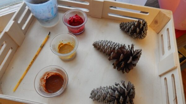 paints mixed with spices, 3 pinecones, paintbrush on wooden tray for Spice Painting Fall activity.