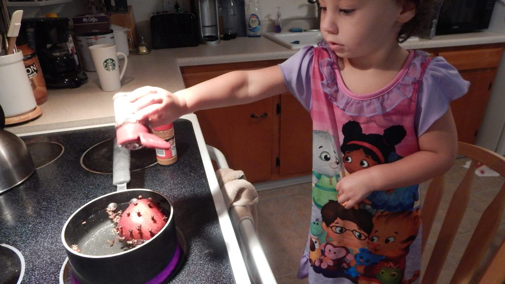 child pouring spices into pot