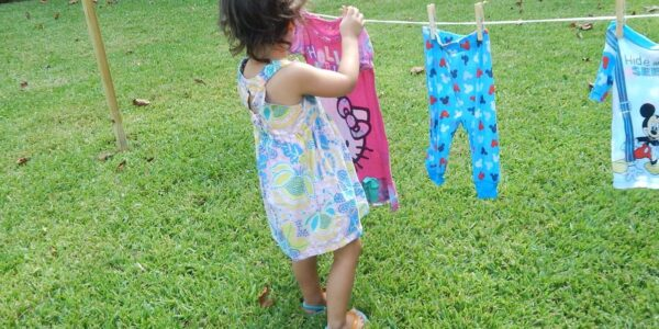 toddler hanging clothes on a line as a Practical Life activity
