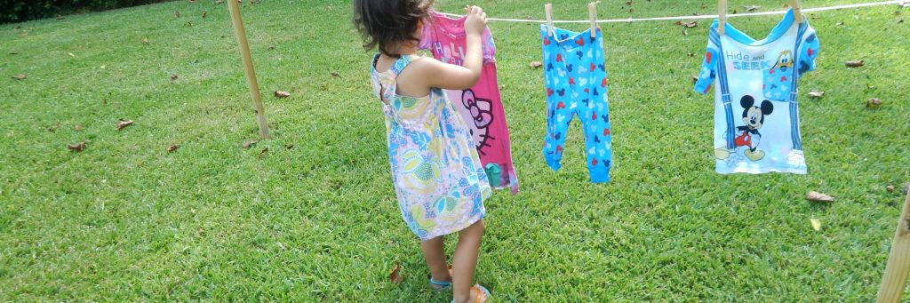 child hanging clothes on child size clothes line.