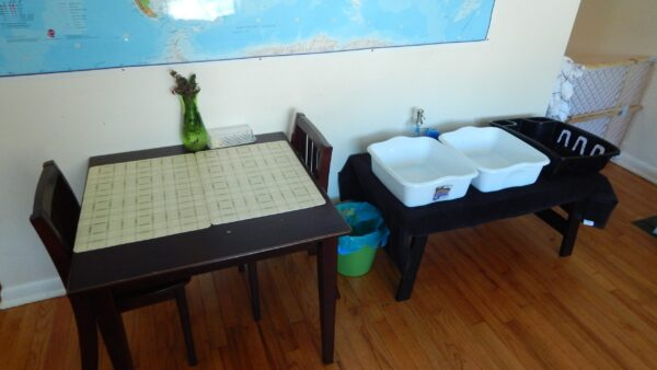 A child's table, next to a dishwashing station for child.