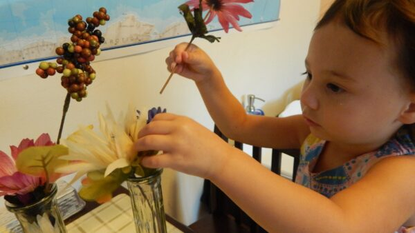 2 year old girl arranging flowers.