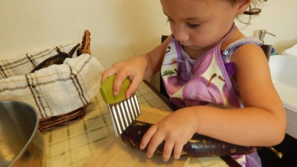 child chopping eggplant, a montessori practical life activity.