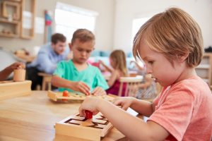 children working in Montessori classroom, building concentration. This may make Montessori worth the price.