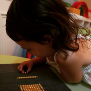 child working with the Golden Bead Material