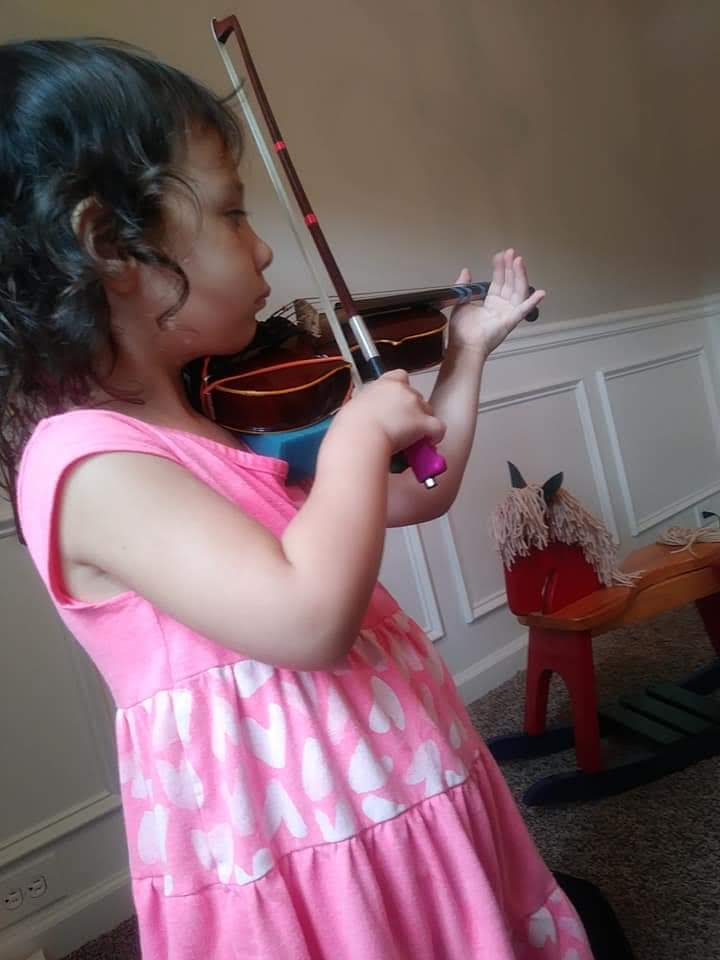 Child playing a violin during the sensitive period for music.