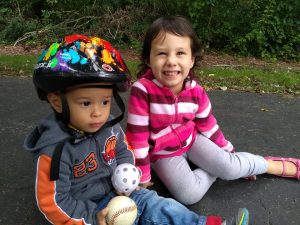 2 kids sitting on the driveway, playing. Montessori: Expectation vs Reality