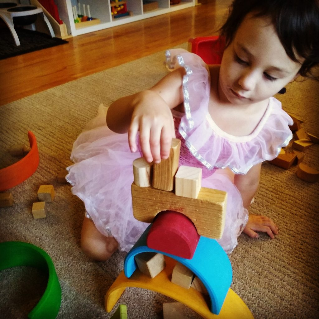 child stacking wooden blocks with Grimm's rainbow pieces.