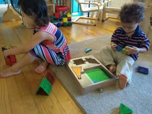 2 young children playing with magna-tiles.