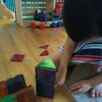 child playing with Magna-tiles, a great Montessori aligned gift.