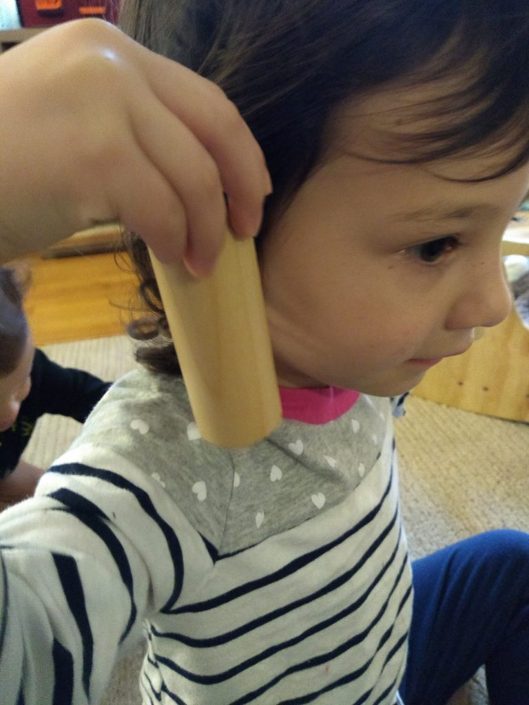 child holding montessori sensory material, sound cylinders.