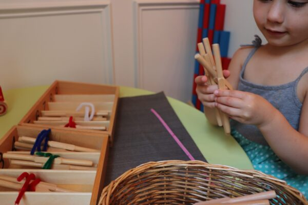 Young girl working with the Montessori Spindle Boxes