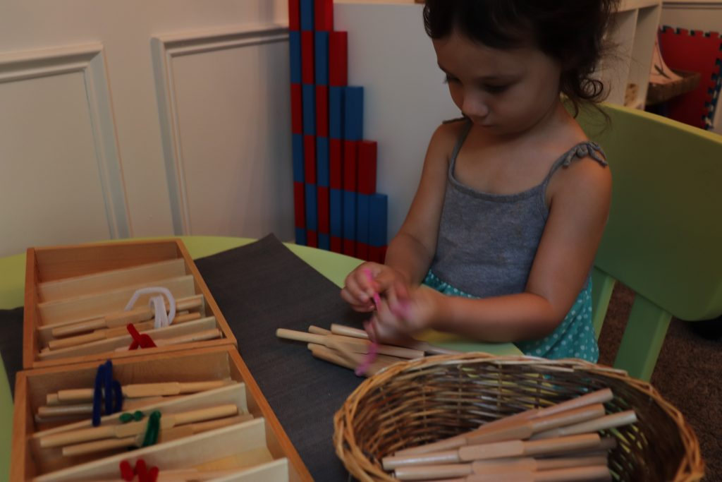 child using Montessori spindle boxes.