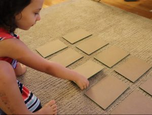sandpaper numbers face down on ground, child about to flip one over during the zero game.
