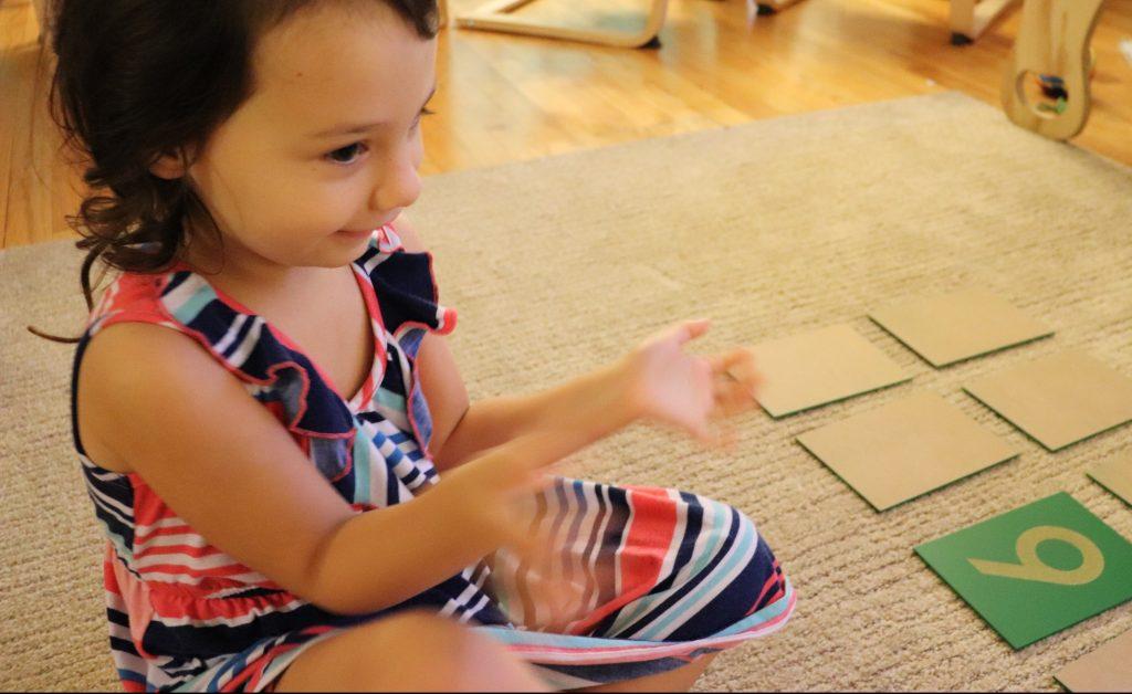 child playing zero game with montessori math materials.ri