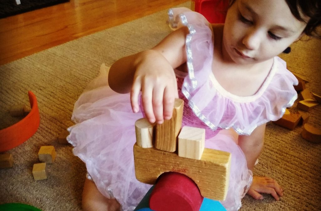 child doing loose parts play by stacking wooden blocks with grimm's rainbow pieces.