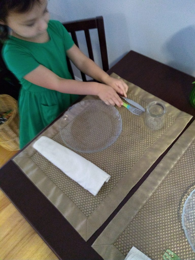 child setting a table.
