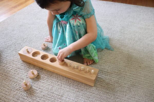 Young child working with the Montessori Knobbed Cylinders