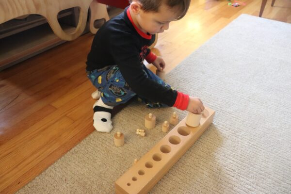 Boy working with the Montessori Knobbed Cylinders