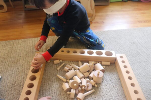 young boy working blindfolded working with the Montessori Knobbed Cylinders