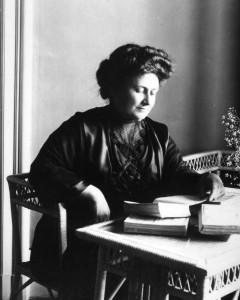 Maria Montessori Facts: black and white photo of Maria Montessori at a desk.