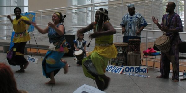 People dancing with people using drums behind them. Use music to teach your child about their cultural heritage.