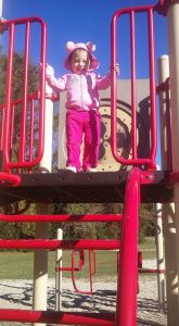 Young toddler playing up high on a playground. This child's mother knows the dangers of helicopter parenting.