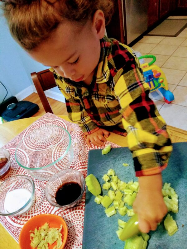 Toddler cutting up vegetables using a wavy chopper.