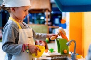 child in montessori play kitchen.