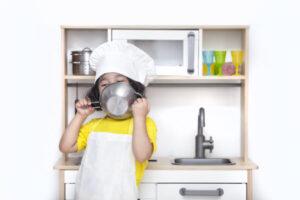 child with ikea Montessori play kitchen.
