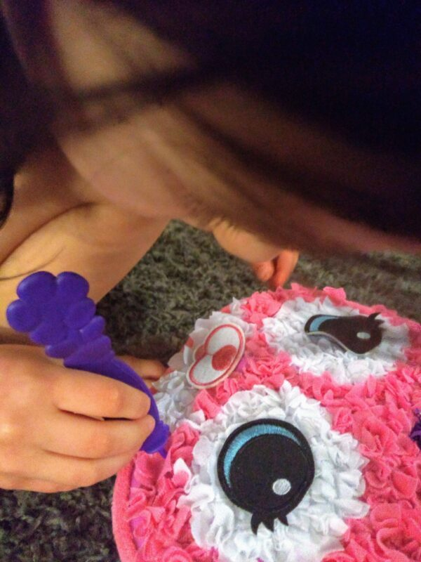 Child pushing pieces of fabric into Cat Pillow Plush Craft Kit using her pincer grasp.