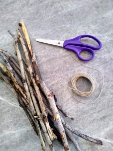 Scissors, twine, and a bundle of twigs.