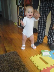 baby taking first assisted steps, proud of herself. An example of why good job is harmful