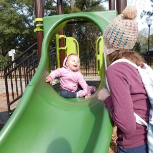 toddler on slide proud of herself. An example of why good job is harmful