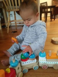infant playing with wooden train on his own