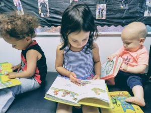 3 young children reading, in Montessori writing before reading is taught.
