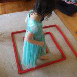 girl walking in between red rods at montessori homeschool, Are Montessori Schools Free?