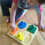 2 year old putting knobbed puzzle together, puzzles are good for fine motor skills and make great Montessori gifts.