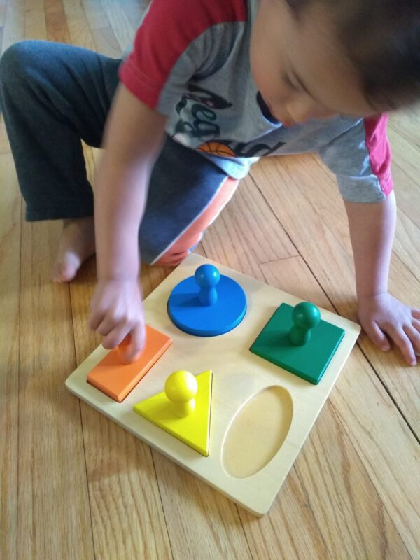 Toddler playing with knobbed puzzle