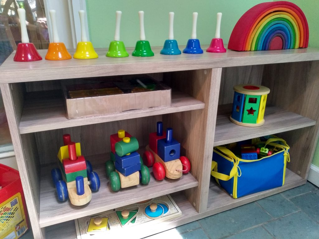 how to organize playroom: bookshelf with rainbow stacker, puzzle, wooden train, sound bells.