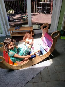 two different age children playing on a rainbow wooden rocker in shared space.