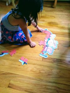 4 year old putting puzzle together. Puzzles are good for you and great STEM toys..
