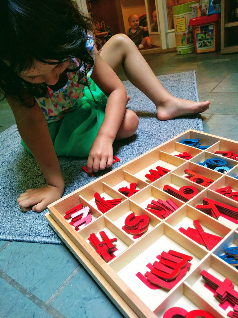 child working with the small movable alphabet in Montessori.