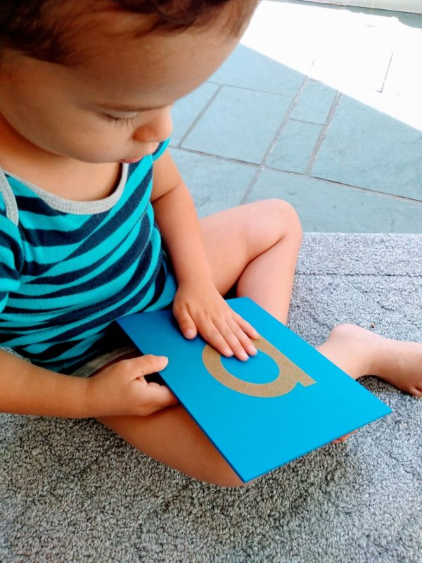 Young boy feeling Sandpaper Letter. Part of a fun Montessori sound game. Used in the sensitive periods for sensation and language/reading/writing.