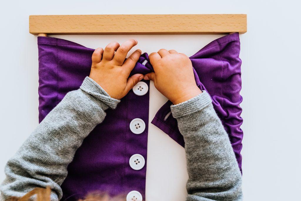 Child using Montessori Button Frame