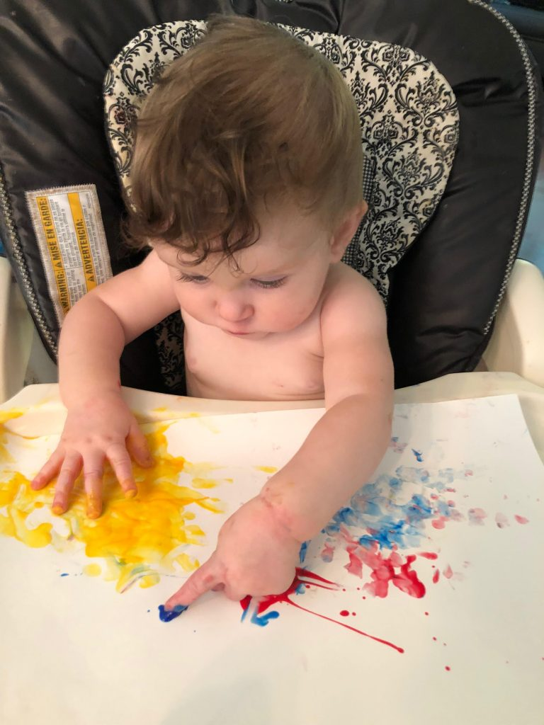 baby fingerpainting to improve fine motor skills.