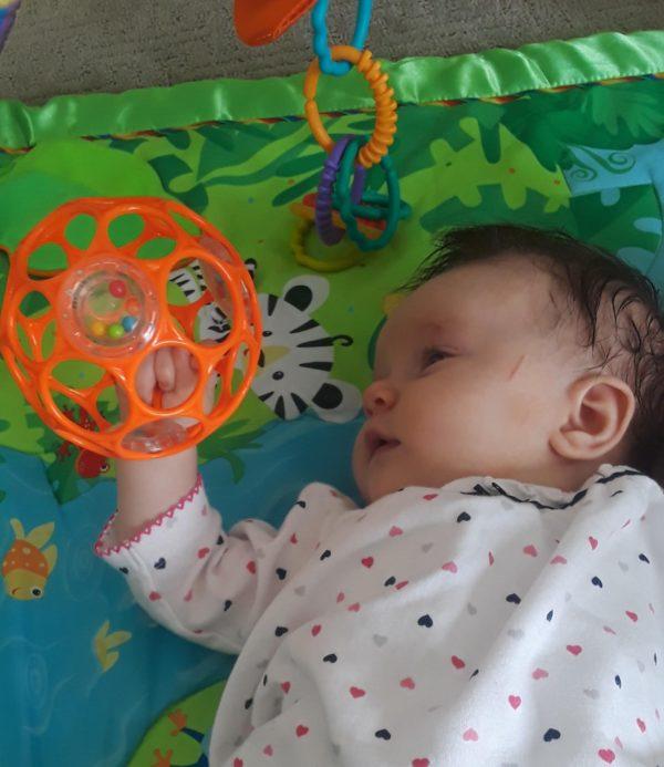 baby grasping O ball
