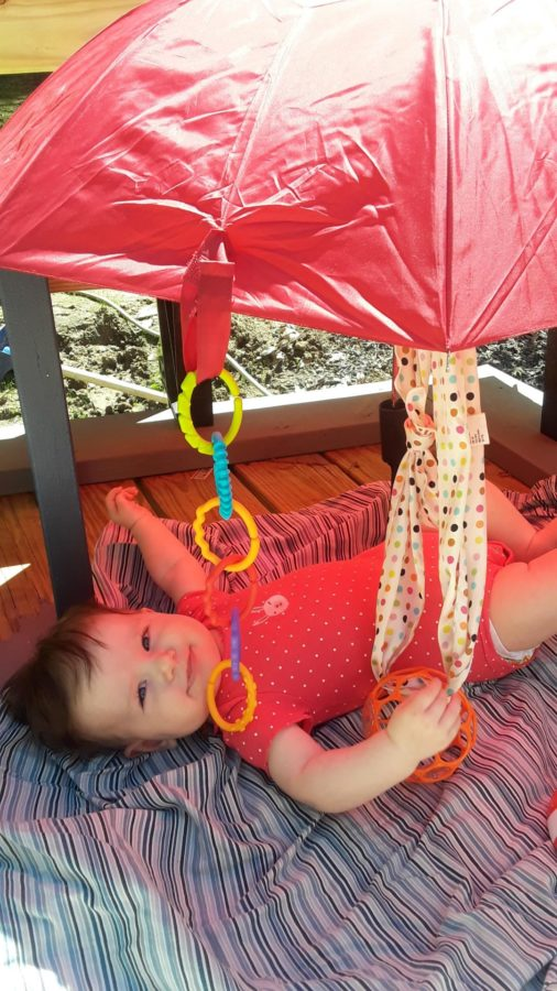 baby outside under umbrella, a gross motor activity